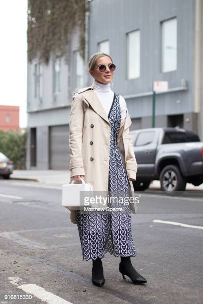 A guest is seen on the street attending SelfPortrait during New York Fashion Week wearing a taupe coat with black/white pattern dress on February 10...