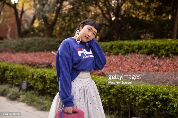 A guest is seen on the street attending Shanghai Fashion Week A/W 2019/2020 wearing blue Fila x DAntidote sweat shirt white spotted pattern skit...