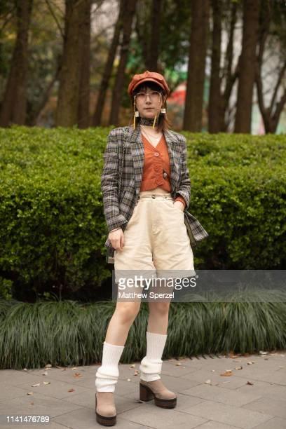 Guest is seen on the street attending Shanghai Fashion Week A/W 2019/2020 wearing grey plaid blazer, rust cardigan and cap, khaki shorts, white socks...