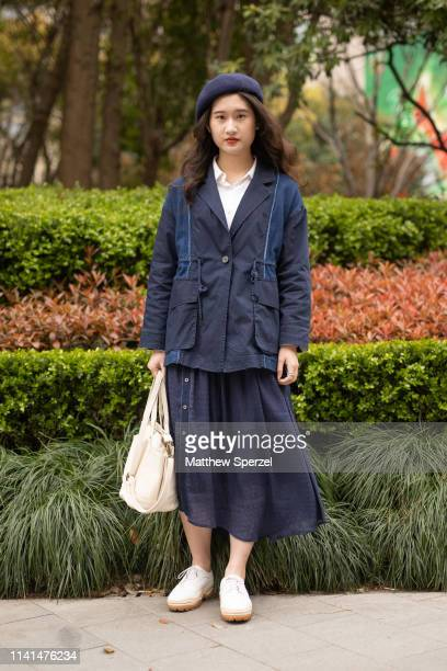 Guest is seen on the street attending Shanghai Fashion Week A/W 2019/2020 wearing navy cargo blazer, navy skirt, navy beret and white bag and shoes...