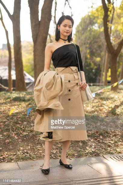 Guest is seen on the street attending Shanghai Fashion Week A/W 2019/2020 wearing black asymmetrical top, khaki skirt, black flats on April 1, 2019...