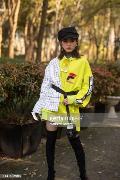 A guest is seen on the street attending Shanghai Fashion Week A/W 2019/2020 wearing white grid pattern shirt black cap neon yellow Fila hoodie black...