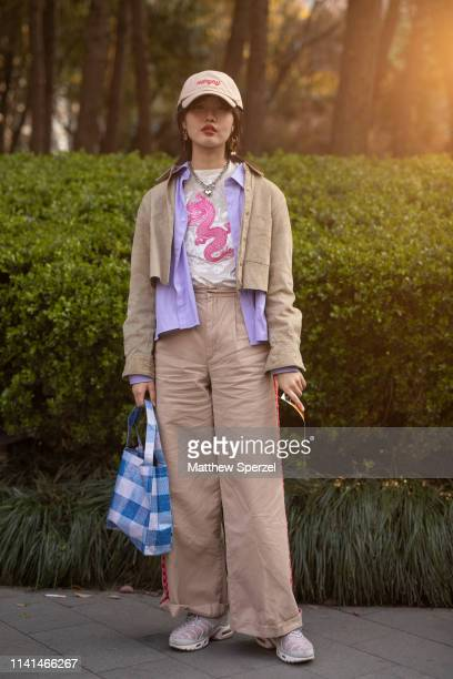 A guest is seen on the street attending Shanghai Fashion Week A/W 2019/2020 wearing khaki jacket and pants purple collared shirt pink dragon shirt...