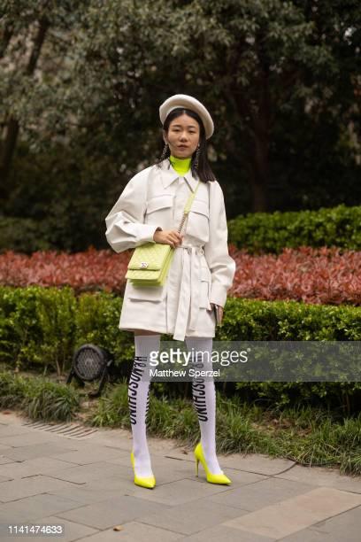 A guest is seen on the street attending Shanghai Fashion Week A/W 2019/2020 wearing white cargo jacket neon green bag neon green turtleneck grey...