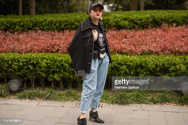 A guest is seen on the street attending Shanghai Fashion Week A/W 2019/2020 wearing black with silver rhinestone jacket black face graphic shirt hip...