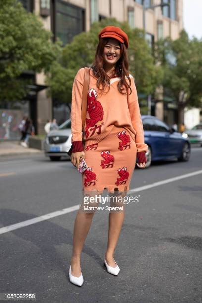 A guest is seen on the street attending Shanghai Fashion Week SS19 wearing orange with red devil pattern sweater and skirt with white shoes and...