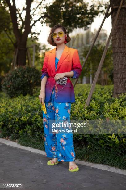 A guest is seen on the street attending Shanghai Fashion Week wearing orange/red/blue blazer blue floral pants hip belt bag yellow sunglasses and...