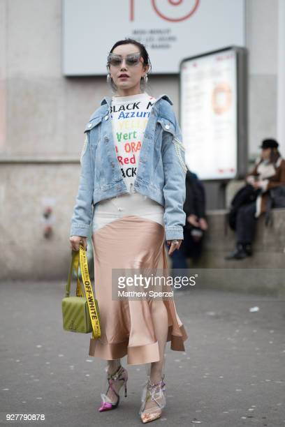 A guest is seen on the street attending Shiatzy Chen during Paris Women's Fashion Week A/W 2018 wearing a denim jacket white rainbow text sweater...