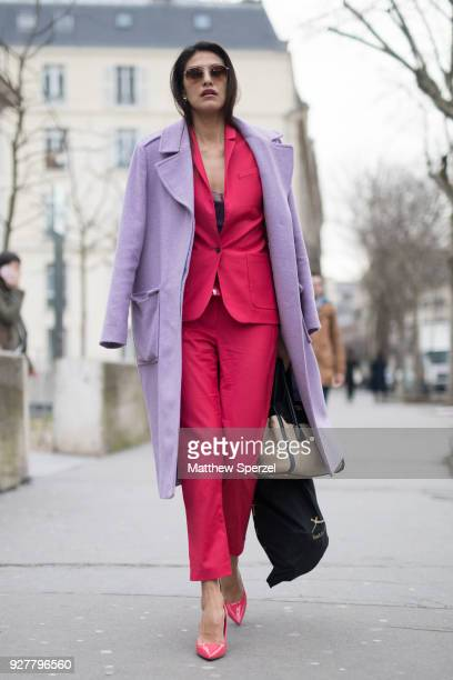 A guest is seen on the street attending Shiatzy Chen during Paris Women's Fashion Week A/W 2018 wearing a pastel purple coat with hot pink suit on...