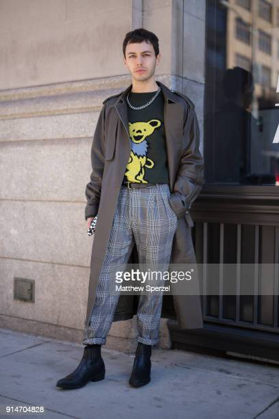 Guest is seen on the street attending Suitsupply during New York Fashion Week Men's wearing a long coat with plaid pants and green sweater with chain...