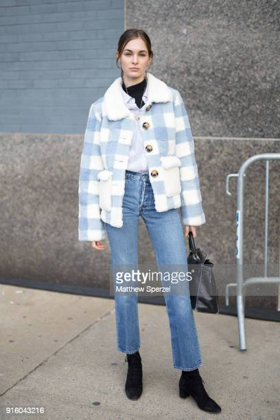 A guest is seen on the street attending Tadashi Shoji during New York Fashion Week wearing a white and blue checker coat with blue jeans on February...