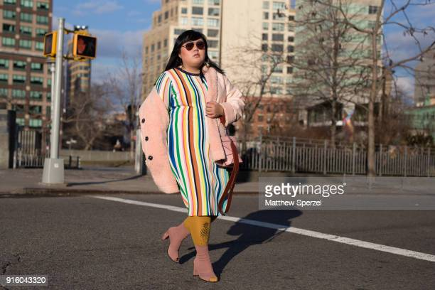 A guest is seen on the street attending Tadashi Shoji during New York Fashion Week wearing a multicolor stripe dress with pink coat on February 8...