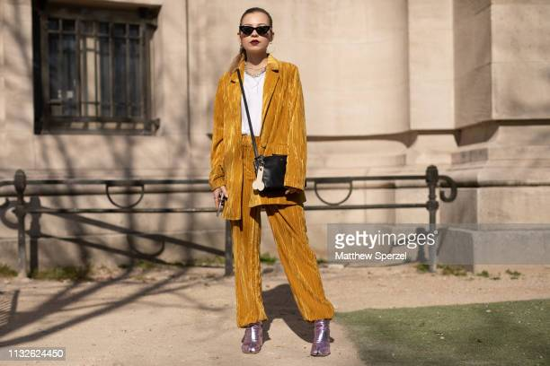 Guest is seen on the street attending Unravel Project during Paris Fashion Week AW19 wearing velvet gold outfit with black bag on February 27, 2019...