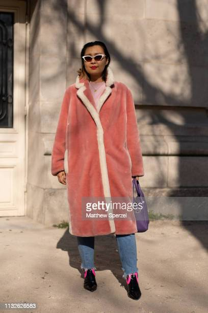 Guest is seen on the street attending Unravel Project during Paris Fashion Week AW19 wearing salmon coat, blue jeans, Prada shoes and purple bag on...