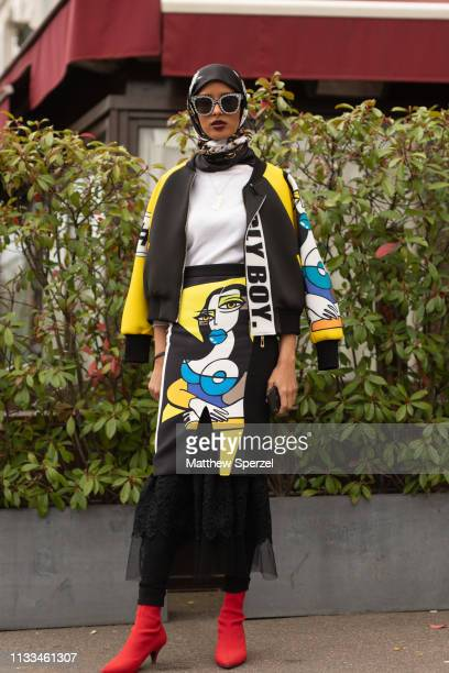 Guest is seen on the street attending VALENTINO during Paris Fashion Week AW19 wearing yellow/black graphic jacket and skirt with red heels and black...