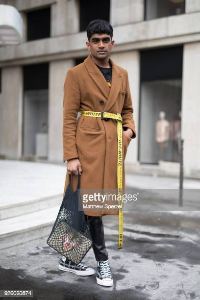 A guest is seen on the street attending Y/PROJECT during Paris Fashion Week Women's A/W 2018 Collection wearing a long tan wool coat with yellow Off...