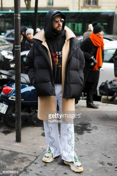 A guest is seen on the street attending Y/PROJECT during Paris Fashion Week Women's A/W 2018 Collection wearing a black down coat tan wool coat black...
