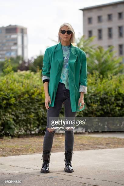 Guest is seen on the street during Berlin Fashion Week wearing aqua green Daily Paper blazer, green/blue tie dye shirt, torn denim jeans, black boots...