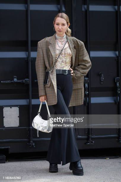 Guest is seen on the street during Berlin Fashion Week wearing grey blazer, gold top, black pants and belt, white bag, phone sling and silver jewelry...