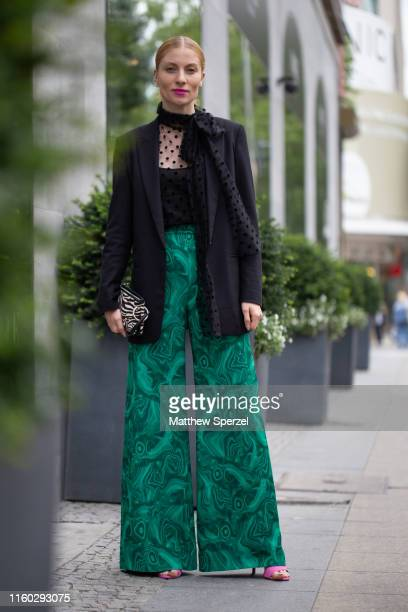 Guest is seen on the street during Berlin Fashion Week wearing navy blazer, lace shirt, navy scarf, turquoise pattern high-waisted pants, pink on...