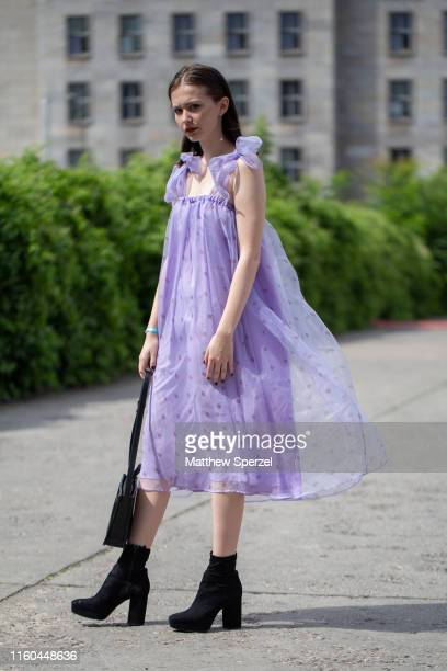 Guest is seen on the street during Berlin Fashion Week wearing pastel purple dress with black heeled boots and black bag on July 06, 2019 in Berlin,...