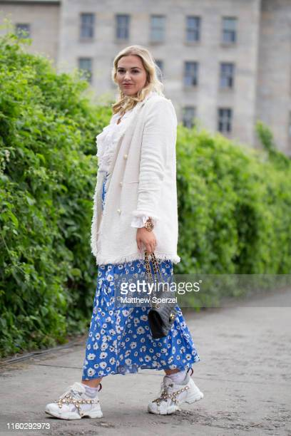 Guest is seen on the street during Berlin Fashion Week wearing white sweater and shirt, blue floral skirt, white Gucci sneakers on July 05, 2019 in...