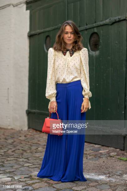 A guest is seen on the street during Copenhagen Fashion Week SS20 wearing polka dot collared shirt blue pants and neon red bag on August 06 2019 in...