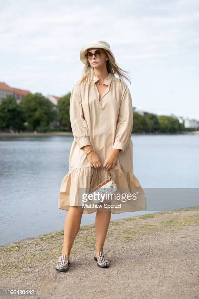Guest is seen on the street during Copenhagen Fashion Week SS20 wearing beige dress with Louis Vuitton bag, Burberry shoes and cream hat on August...