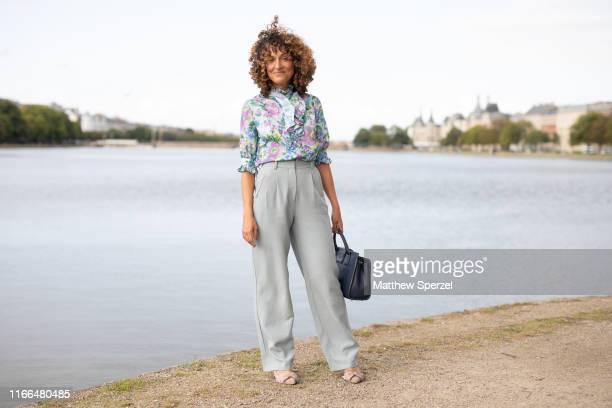 A guest is seen on the street during Copenhagen Fashion Week SS20 wearing floral pattern shirt grey pants black bag on August 06 2019 in Copenhagen...