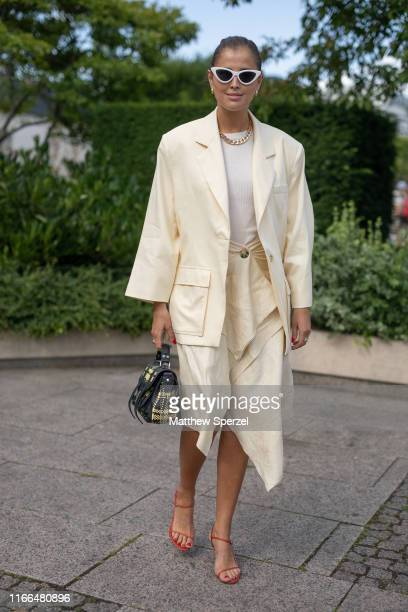 Guest is seen on the street during Copenhagen Fashion Week SS20 wearing cream oversized blazer and skirt, white shirt, gold chain necklace, white...