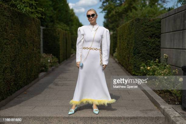 Guest is seen on the street during Copenhagen Fashion Week SS20 wearing white dress with yellow fur trim, gold chain belt, Jacquemus mini blue bag...