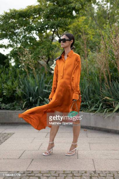 Guest is seen on the street during Copenhagen Fashion Week SS20 wearing orange silk dress, green/red bag, white heels and sunglasses on August 06,...