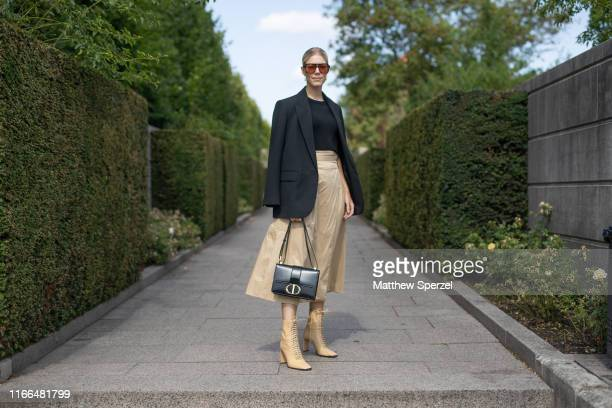 Guest is seen on the street during Copenhagen Fashion Week SS20 wearing black blazer and top, taupe skirt and shoes, black bag on August 06, 2019 in...