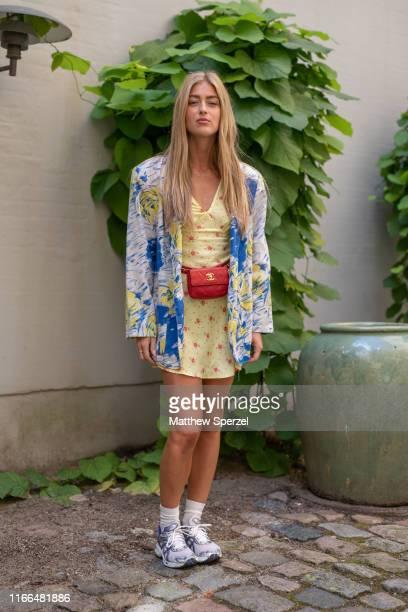 A guest is seen on the street during Copenhagen Fashion Week SS20 wearing blue/yellow pattern jacket yellow/red pattern dress red hip belt bag...