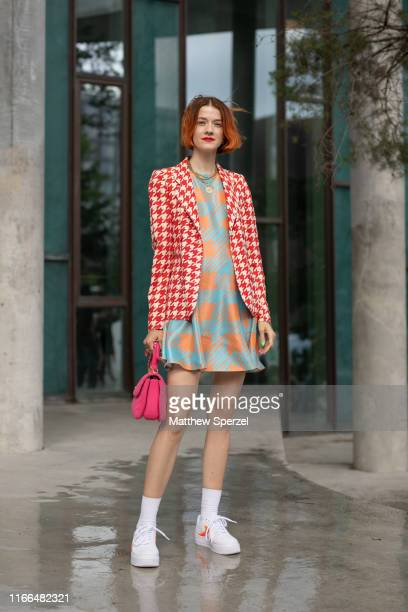 A guest is seen on the street during Copenhagen Fashion Week SS20 wearing red/white pattern blazer blue/orange pattern dress hot pink bag white...