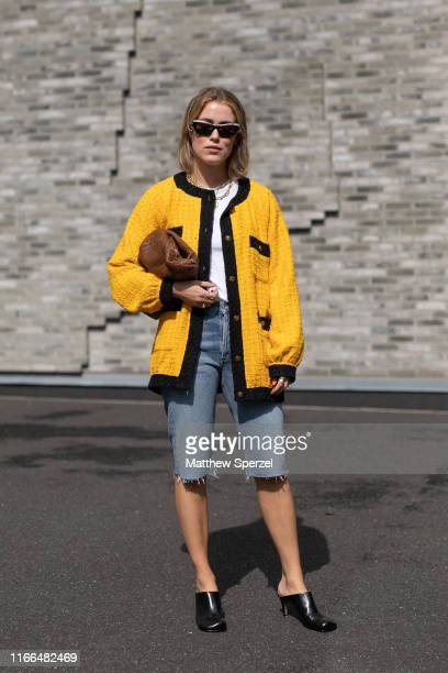 A guest is seen on the street during Copenhagen Fashion Week SS20 wearing yellow/black cardigan cutoff jeans white shirt black heels on August 06...