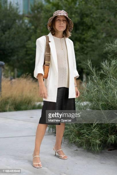 Guest is seen on the street during Copenhagen Fashion Week SS20 wearing white blazer, cream top, black skirt, bucket hat on August 06, 2019 in...