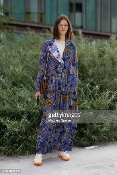 A guest is seen on the street during Copenhagen Fashion Week SS20 wearing blue/copper/navy floral pattern suit with white shirt grey sneakers on...