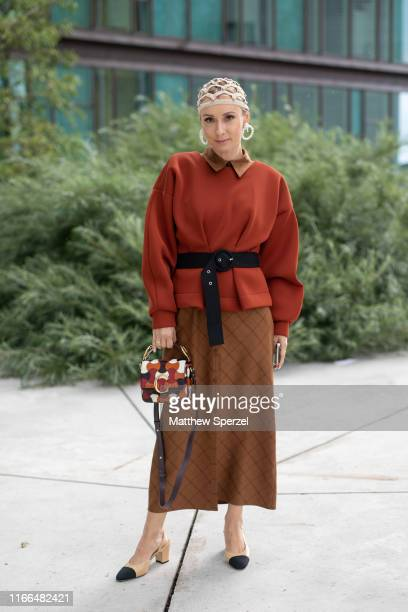 Guest is seen on the street during Copenhagen Fashion Week SS20 wearing rust sweater, copper collared shirt and skirt, black belt, taupe hair net,...
