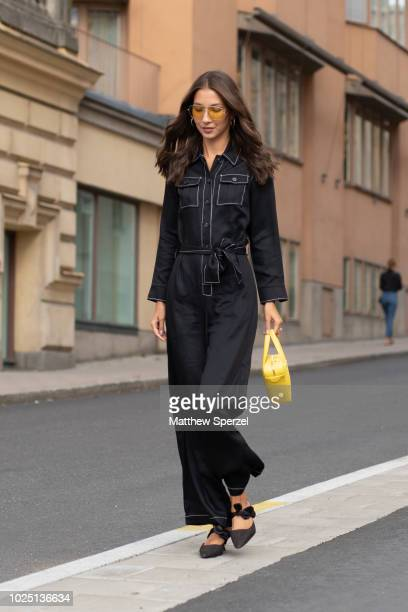 A guest is seen on the street during Fashion Week Stockholm SS19 wearing a black jumpsuit with yellow bag on August 29 2018 in Stockholm Sweden