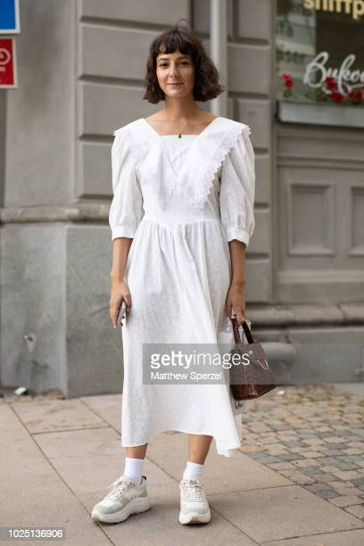 A guest is seen on the street during Fashion Week Stockholm SS19 wearing a white dress on August 29 2018 in Stockholm Sweden
