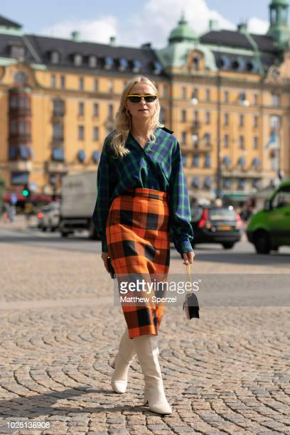 A guest is seen on the street during Fashion Week Stockholm SS19 wearing a navy/green plaid shirt with orange plaid skirt on August 29 2018 in...