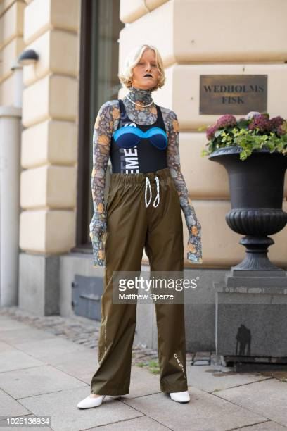 A guest is seen on the street during Fashion Week Stockholm SS19 wearing a floral pattern turtleneck Vetements bodysuit blue outer bra and olive...