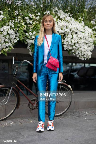 A guest is seen on the street during Fashion Week Stockholm SS19 wearing a metallic blue suit with red shoulder bag and sneakers on August 30 2018 in...