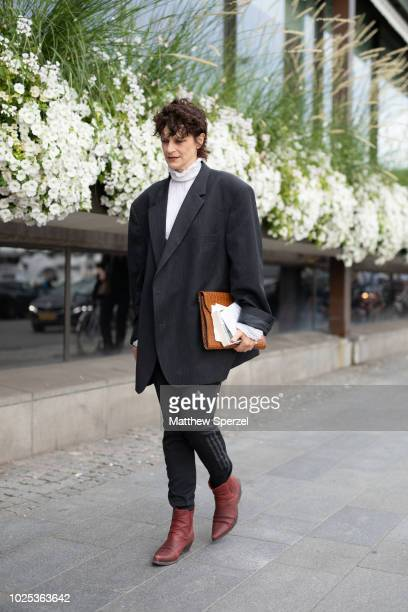 A guest is seen on the street during Fashion Week Stockholm SS19 wearing an oversized blazer with turtleneck and Adidas track pants on August 30 2018...