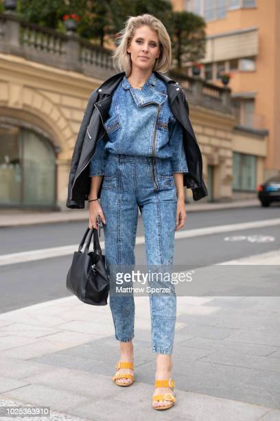 A guest is seen on the street during Fashion Week Stockholm SS19 wearing black leather jacket with denim jumpsuit on August 30 2018 in Stockholm...