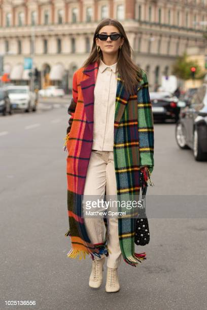 A guest is seen on the street during Fashion Week Stockholm SS19 wearing twotone colorful plaid coat with cream outfit on August 29 2018 in Stockholm...