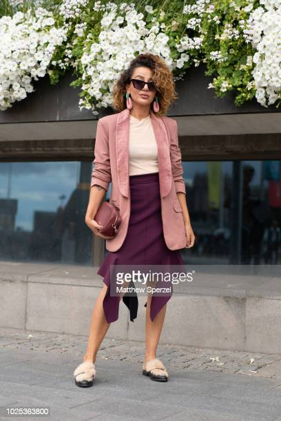 A guest is seen on the street during Fashion Week Stockholm SS19 wearing pink blazer and earrings cream shirt maroon skirt and fur sandals on August...