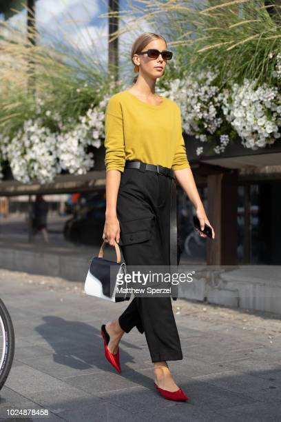 Guest is seen on the street during Fashion Week Stockholm wearing a yellow sweater with black cargo pants and red heels on August 28, 2018 in...