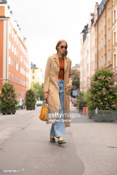 A guest is seen on the street during Fashion Week Stockholm wearing a long camel coat rust sweater and faded denim jeans on August 28 2018 in...
